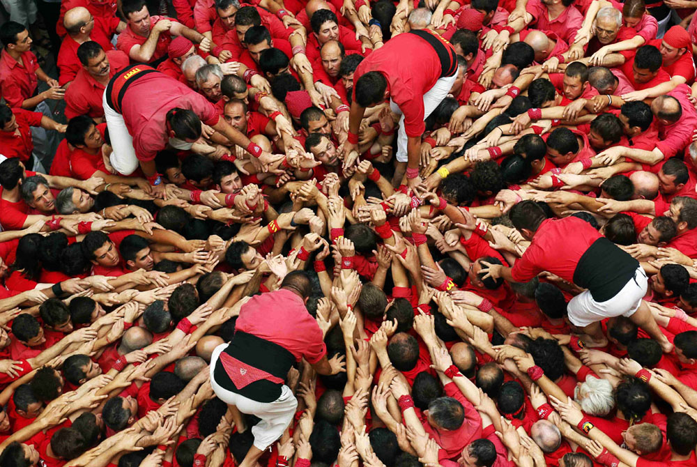 "Castellers Colla Joves Xiquets de Valls start to form a human tower called ""castells"" during the Sant Joan festival at Plaza del Blat square in Valls"
